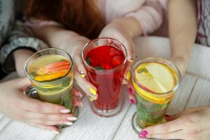 Delicious fruit mocktails in female hands. The concept of a drink, meeting.